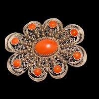 A showy ornate 800 silver filigree salmon coral pin.