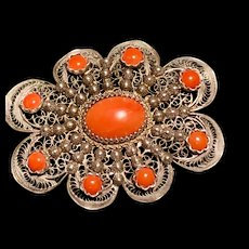 A showy ornate 800 silver filigree salmon coral pin.