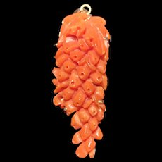 A finely carved estate salmon momo coral 14k pendant