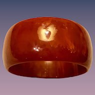 A vintage chunky carnelian colored bakelite bangle