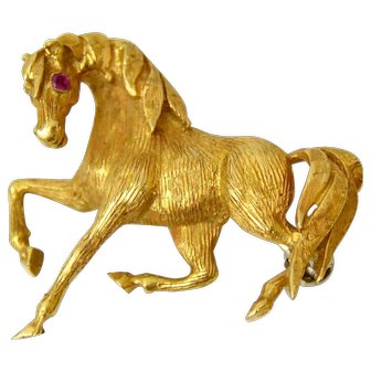 A Beautiful and Stylish Vintage Galloping Horse Brooch. Italy, 1960-70. 18 ct gold, natural rubies.