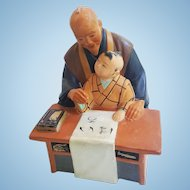 A vintage Hakata Urasaki hand painted sculpture of man and grandson practicing calligraphy. FREE US SHIPPING