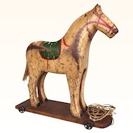Wooden toy horse on metal wheeled base