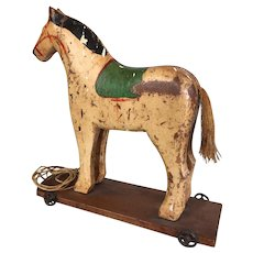 Wooden toy horse pull toy on metal wheeled base