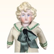 Tinted bisque doll with blonde molded hair and wonderful clothing