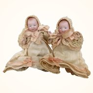Pair of exquisite miniature German all bisque Bye-Lo babies in matching clothing