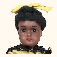 Rare and lovely black miniature doll in yellow dress and boots