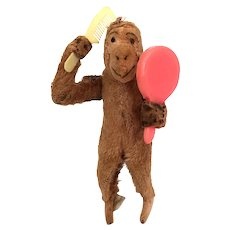 Vintage windup toy monkey combing hair