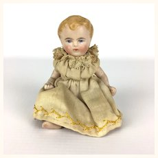 Adorable miniature all bisque baby in original clothing
