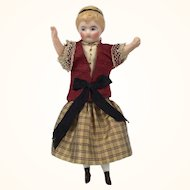 Antique dollhouse girl in lovely clothing and unusual posture