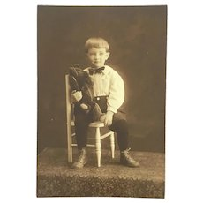 Antique sepia photo of little boy with his teddy bear