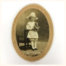 Antique sepia photo of child with teddy bear