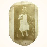 Very old photograph postcard of little girl with teddy bear and flowers