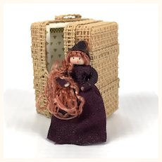 Miniature dollhouse straw trunk with tiny doll inside it