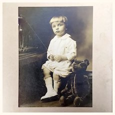 Antique photo of little boy with large teddy bear