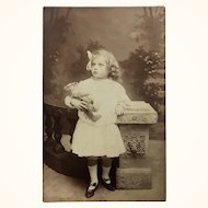 Antique sepia toned postcard photograph of well dressed child and her teddy bear