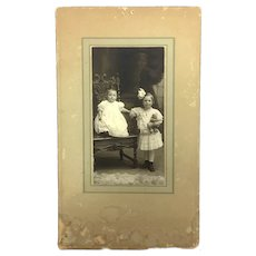 Antique sepia tone photograph of two children and a teddy bear
