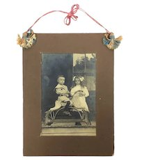Antique sepia tone photograph of brother, sister and hobby horse