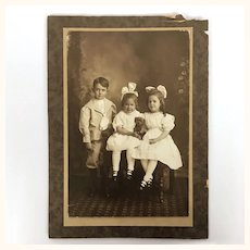 Antique sepia Tone photograph of three children and a teddy bear
