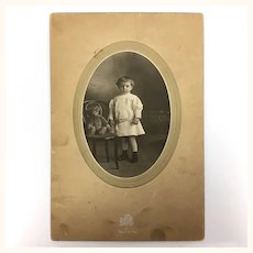 Antique sepia tone photo of little boy and teddy bear