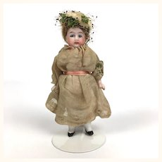 Antique all bisque little girl in grown up hat