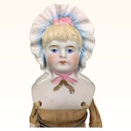 Bonnet head parian doll with gold bow