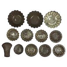 Twelve antique tin tart and tartlet tins