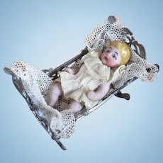 Dollhouse German bisque baby in soft metal miniature cradle