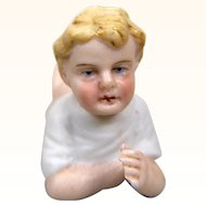 Antique porcelain piano baby, pink tinted boy