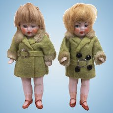 Pair of miniature girl all bisque dolls in adorable clothing