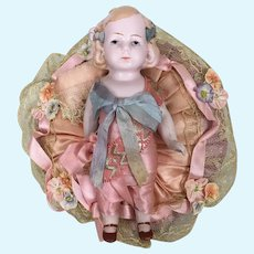 Vintage German all bisque doll on pincushion or pillow