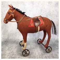 Antique felt toy horse on cast iron wheels