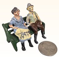 Antique miniature cast iron people on bench