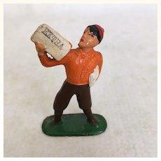 Antique cast metal miniature newsboy in orange sweater