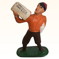 Antique cast metal miniature newsboy in orange sweater