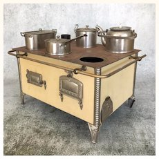 Antique miniature tin stove with pots and pans