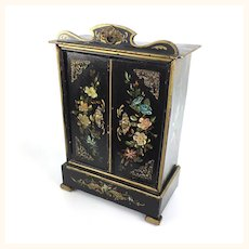 Antique doll's cupboard with hand-painted floral design