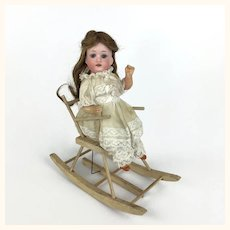 Antique doll in windup rocking chair