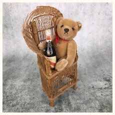 Vintage Steiff teddy bear in chair with champagne bottle