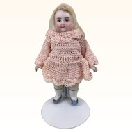 Miniature all bisque girl in pink crocheted dress