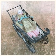 Ornate metal baby carriage with sweet all bisque baby doll