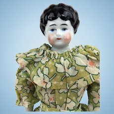 China head small lowbrow doll on original body with lovely clothing