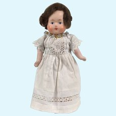Vintage Small papier mache doll with painted face and sweet little dress