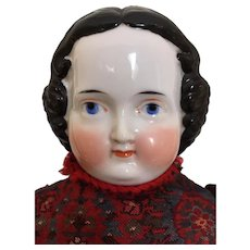 Antique china flattop doll with unusual sweet face and clothing