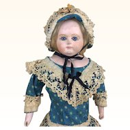 Papier mache fashion doll with glass eyes and beautiful clothing