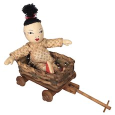 Tiny Chinese cloth doll in toy wagon