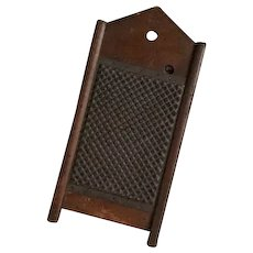 Hand punched tin grater in wooden frame with peaked top and legs