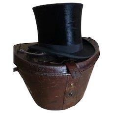 Antique black silk top hat, leather hat box