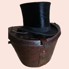 Antique black silk top hat, leather hat box