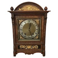 An oak cased mantel clock with a brass dial